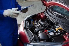 Mechanic holding clipboard in front of open car engine Stock Photos