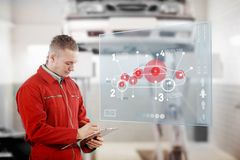 Mechanic holding a clipboard with a futuristic interface next to Stock Images