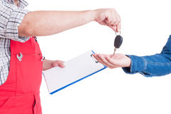 Mechanic holding clipboard and handing car key to customer Stock Images
