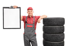 Mechanic holding a clipboard and leaning on tires Stock Image
