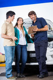 Mechanic Holding Clipboard While Standing With Couple Royalty Free Stock Image