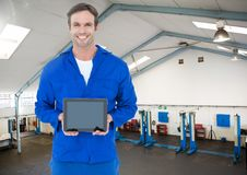 Mechanic holding a digital tablet against workshop in background. Composite image of mechanic holding a digital tablet against workshop in background Stock Photography