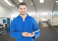 Mechanic holding digital tablet in garage Royalty Free Stock Photo