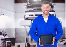 Mechanic holding digital tablet in garage. Smiling mechanic holding digital tablet in garage Royalty Free Stock Photos