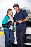 Mechanic Holding Digital Tablet While Standing. Portrait of happy mechanic holding digital tablet while standing with female customer in garage Stock Image