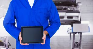 Mechanic holding a digital tablet at workshop. Mid section of mechanic holding a digital tablet at workshop Royalty Free Stock Photo
