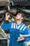 Mechanic Holding Flashlight While Examining Car Exhaust System Royalty Free Stock Photo