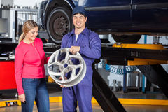 Mechanic Holding Hubcap With Customer Examining It. Portrait of happy mechanic holding alloy with female customer examining it at garage Royalty Free Stock Photo