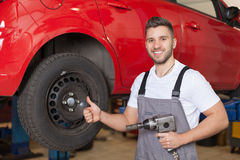 Mechanic holding an impact wrench and showing thumb up Royalty Free Stock Photography