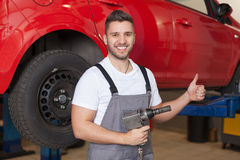 Mechanic holding an impact wrench and showing thumb up Stock Images
