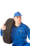 Mechanic is holding one car tire Royalty Free Stock Image