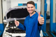 Mechanic holding pair of wrenches Stock Images