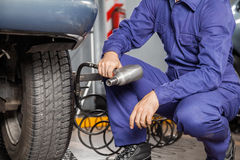 Mechanic Holding Pneumatic Wrench By Car. Midsection of male mechanic holding pneumatic wrench by car at garage royalty free stock photos