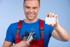 Mechanic holding selection of spanners and business card. Royalty Free Stock Images