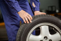Mechanic Holding Tire At Garage Stock Image