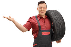 Mechanic holding a tire and gesturing with his hand royalty free stock images