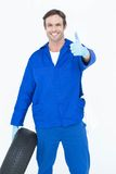 Mechanic holding tire while showing thumbs up. Portrait of confident mechanic holding tire while showing thumbs up over white background Royalty Free Stock Photography