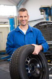 Mechanic holding a tire wheel Royalty Free Stock Photos