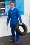 Mechanic holding a tire wheel. At the repair garage Stock Photos