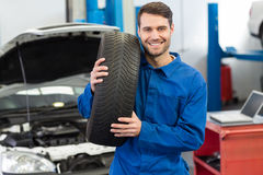 Mechanic holding a tire wheel Royalty Free Stock Images