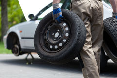 Mechanic holding a two car wheel Royalty Free Stock Photo
