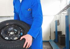 Mechanic holding tyre in repair garage Royalty Free Stock Image