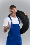 Mechanic holding vehicle tire on grey background. Royalty Free Stock Photography