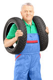 Mechanic holding a vehicle tires and looking at camera Stock Images