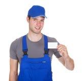 Mechanic holding visiting card Royalty Free Stock Photos