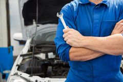Mechanic holding wrench with crossed arms Stock Photos