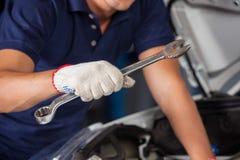 Mechanic Holding Wrench While Examining Car Engine royalty free stock photos