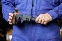 Mechanic Holding Wrench In Repair Shop stock photography