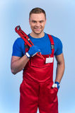 Mechanic holding wrench and wearing blank badge card. Stock Photos