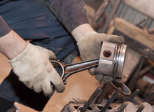 The mechanic holds the piston in hand Stock Images