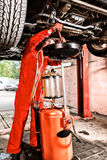 Mechanic hooking up equipment to a car. Mechanic hooking up equipment to the undercarriage of a car elevated on a hoist during repairs and maintenance in a Stock Photos