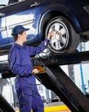 Mechanic Inflating Car Tire At Garage stock photo