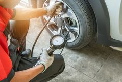 Mechanic inflating put air into the tyre and checking air pressure with gauge pressure. Close up mechanic inflating put air into the tyre and checking air royalty free stock photography