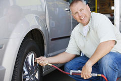 Mechanic Inflating RV~s Tire. Portrait of a happy male mechanic inflating RV~s tire Royalty Free Stock Image