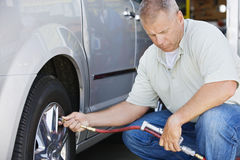 Mechanic Inflating RV~s Tire. Male mechanic inflating RV~s tire Royalty Free Stock Photography