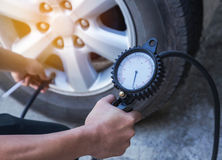 Mechanic inflating tire and checking air pressure with gauge. Close up mechanic inflating tire and checking air pressure with gauge pressure Stock Images