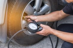 Mechanic inflating tire and checking air pressure with gauge pressure. Close up mechanic inflating tire and checking air pressure with gauge pressure in service Stock Images