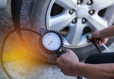 Mechanic inflating tire and checking air pressure with gauge pressure. Close up mechanic inflating tire and checking air pressure with gauge pressure Royalty Free Stock Image
