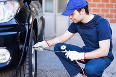 Mechanic inflating a tire Royalty Free Stock Photography