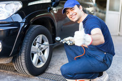 Mechanic inflating a tire Stock Photography