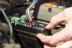 The mechanic inserts a new fuse into the socket using the pliers. Stock Photos