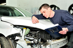 Mechanic inspecting car body damage at auto repair shop service Royalty Free Stock Images