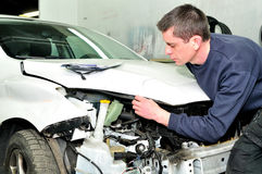 Mechanic inspecting car body damage at auto repair shop service Stock Photos
