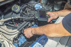 Mechanic inspecting car engine with video borescope royalty free stock photos
