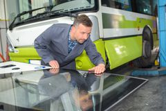 Mechanic inspecting new panel for bus royalty free stock images