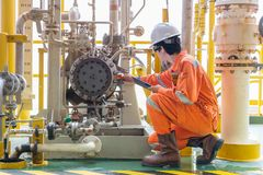 Mechanic inspector engineer check condition of crude oil centrifugal pump and lube oil system at offshore gas platform royalty free stock image